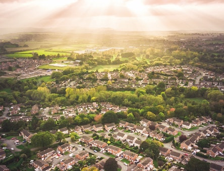 Aerial view looking down across a town with beams of sunlight visible
